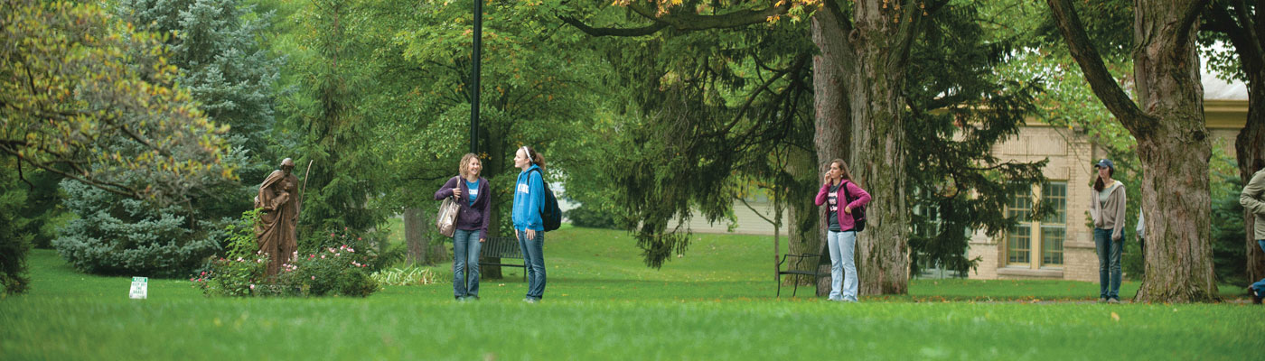 a group of USF students walking between Trinity Hall and Brookside